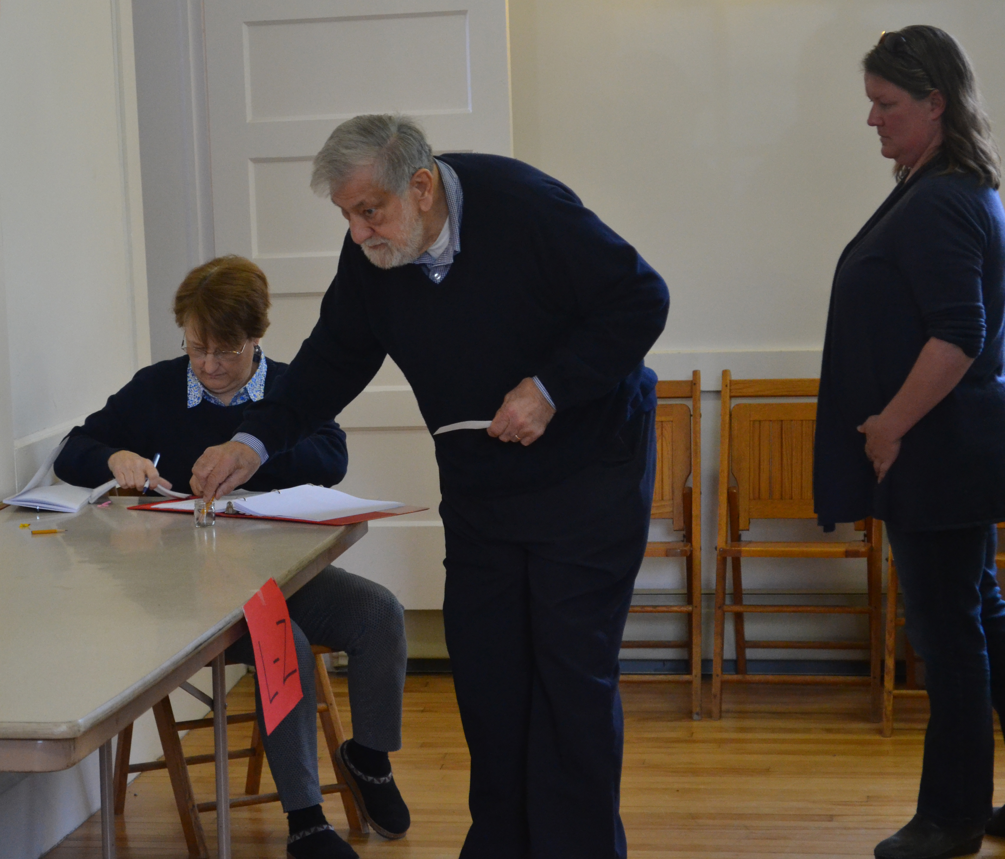 Edgecomb Board of Selectmen Chair Jack Sarmanian votes by secret ballot on an education budget warrant article at the annual town meeting Saturday, May 13, with new Edgecomb School Committee member Heather Sinclair next in line. (Abigail Adams photo)