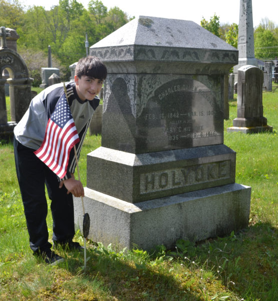 Edgecomb Eddy School sixth-grader Anthony Gelormine places a flag on a veteran's grave at the North Edgecomb Cemetery on Tuesday, May 23. (Abigail Adams photo)