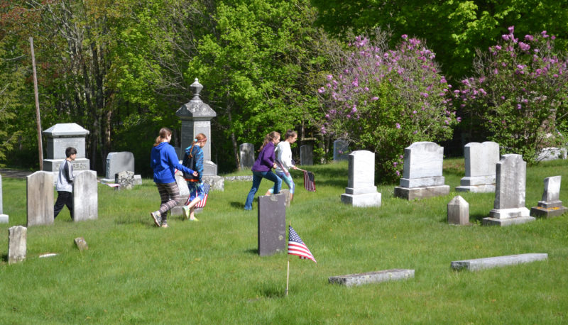 Edgecomb Eddy School sixth-graders search for veterans' gravestones to place flags on in honor of Memorial Day at the North Edgecomb Cemetery on Tuesday, May 23. (Abigail Adams photo)