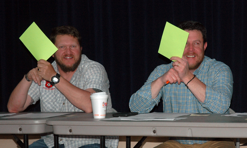 Jefferson School Committee members Walter Greene-Morse (left) and Forrest Bryant raise their placards in support of a warrant article during the education budget meeting at Jefferson Village School on Tuesday, May 23. (Alexander Violo photo)