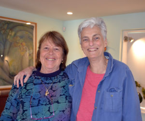 Damariscotta artist Marnie Sinclair (left) and her friend Deb Poor are all smiles in the dining-room-turned-art gallery on the first floor of Poor's River Road home. (Christine LaPado-Breglia photo)