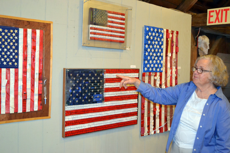 """Damariscotta artist Franciska Needham motions to """"American Flag in Computer Parts II,"""" one of a number of creatively designed U.S. flags on display at her current show, """"America the Beautiful,"""" at her 200-year-old barn-turned-gallery on Water Street. (Christine LaPado-Breglia photo)"""