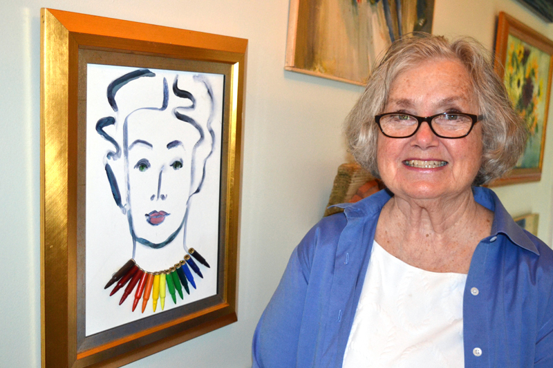"""Franciska Needham stands beside an earlier self-portrait that hangs inside her home, which is adjacent to her Water Street art gallery. Needham said she added the rainbow-colored bullet necklace """"because no matter where I was in the world, they'd know I was American, because we're gun people."""" (Christine LaPado-Breglia photo)"""