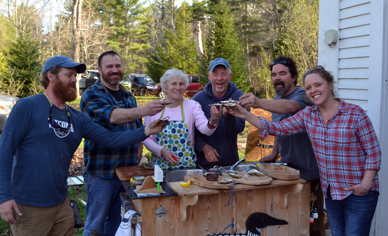 "From left: Chase Morrill, Adam Myer, Sharon and Leigh Morrill, Ryan Eldridge, and Ashley Morrill-Eldridge enjoy oysters at the Morrills' home after completing filming for ""Maine Cabin Masters"" for the day Friday, April 28. (Abigail Adams photo)"