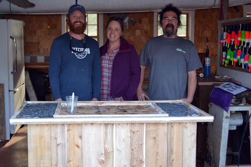 "From left: ""Maine Cabin Masters"" Chase Morrill, Ashley Morrill-Eldridge, and Ryan Eldridge stand in front of a mobile shucking station built for a cabin at Glidden Point Oyster Farms on Friday, April 28. (Abigail Adams photo)"