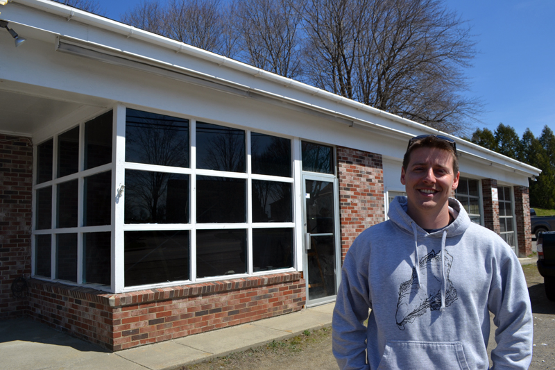 Brendan Parsons stands in front of Damariscotta River Distribution at 68 Main St. in Newcastle. Parsons opened the oyster distribution business in March and is in the process of converting the rest of the building into a raw bar and retail shop, The Shuck Station. (Maia Zewert photo)