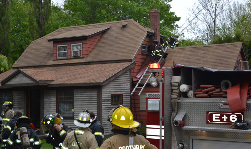 Firefighters cut out an area of roof and wall around the chimney of a Flood Avenue home to prevent the spread of a fire the afternoon of Monday, May 22. (Abigail Adams photo)