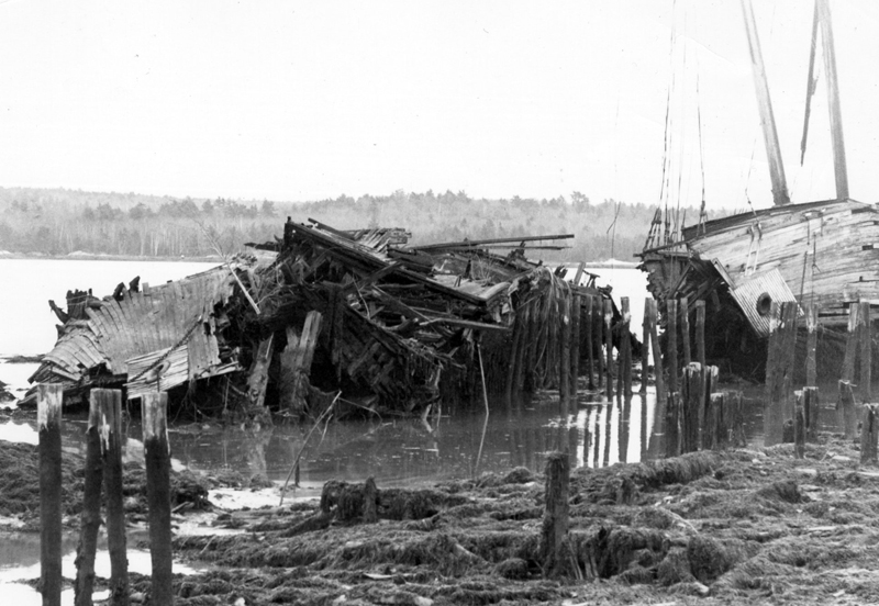 The Hesper, a four-masted schooner built in the early 1900s, appears as a pile of picked-over rubble on the Wiscasset waterfront in this 1990 photograph. At right is the Luther Little. (LCN file photo)