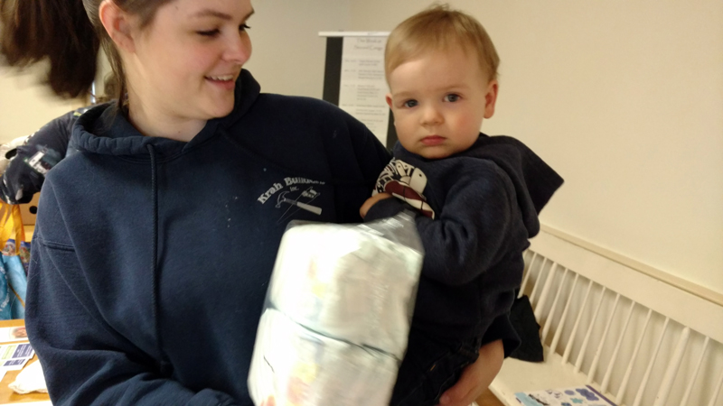 Volunteers Emily and Raylan Krah help distribute diaper packets at the Ecumenical Food Pantry in Newcastle. (Photo courtesy Sue Rockwood)