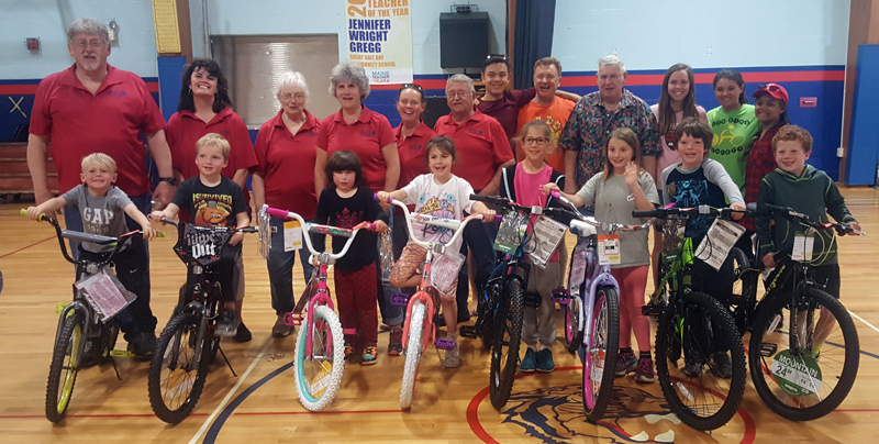 Back from left: bus drivers John Mitkus, Camille Chadwick, Charlotte Simmons,  Debby Newell, Maggie Quinlan, and Allan Ray with volunteers Dylan DeFosses, David DeFosses, Gordon Benner, Hanna Fake, Rachel DeFosses, and Rowena DeFosses. Front from left: bicycle winners Madox Gregory, William Nery, Ava Ward, Rosie Adams, Maggie Thompson, Brooke McFarland, Atticus Donaghy, and Camden McCool. (Remy Segovia photo)