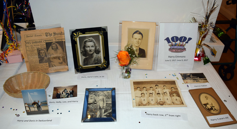 A table at Harry Emmons' 100th birthday party includes photos from his life, as well as his engagement and wedding announcements. (J.W. Oliver photo)