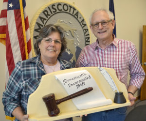 """Damariscotta Board of Selectmen Chair Robin Mayer and Vice Chair Ronn Orenstein hold a 1959 wood carving by the late Damariscotta artist Maurice """"Jake"""" Day. The carving, along with the town seal behind Mayer and Orenstein, were both carved by Jake Day in 1959 and restored by his grandson Dan Day. (Maia Zewert photo)"""