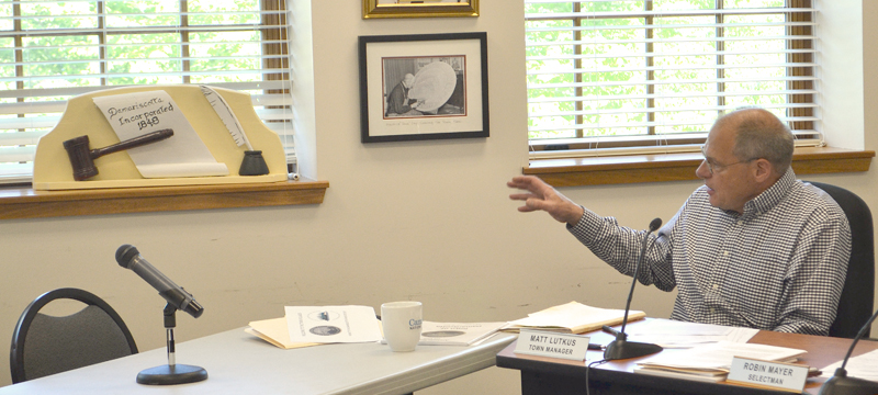 "Damariscotta Town Manager Matt Lutkus points out a recently restored 1959 wood carving by the late Damariscotta artist Maurice ""Jake"" Day during a Damariscotta Board of Selectmen meeting Wednesday, June 7. (Maia Zewert photo)"