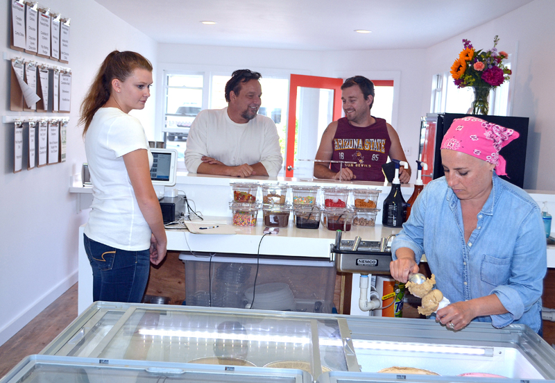 Wicked Scoops employee Brooke Seiders (left) looks on as owner Jamie Way (right) scoops ice cream on the business's opening day, Friday, June 23, while customers Joe Jacobs (left) and William Bradford chat at the counter. (Maia Zewert photo)