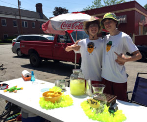 Friends and business partners Dylan Squiers (left) and Dawson French at their lemonade stand, Sugar Daddy's Lemonade, in Damariscotta on Monday, June 12. French designed and made their shirts. (Maia Zewert photo)