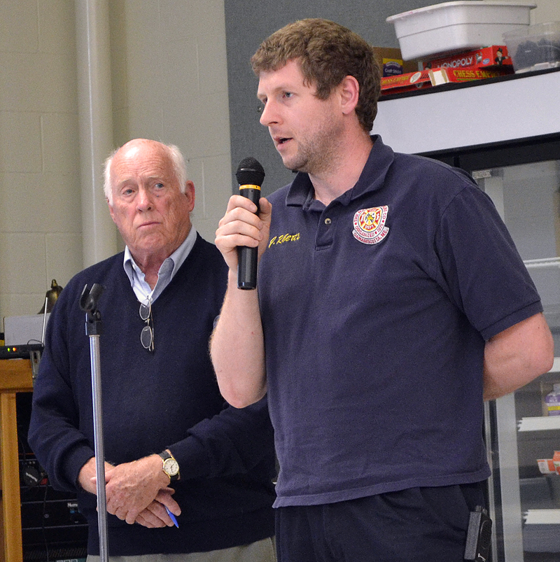 Moderator Don Means (left) looks on as Damariscotta Fire Chief John Roberts talks about the department's fundraising efforts during annual town meeting Wednesday, June 14. (Maia Zewert photo)
