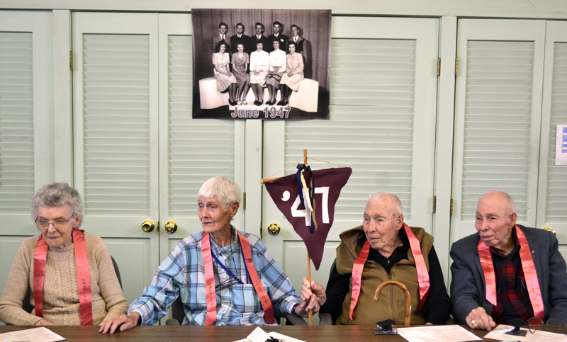 From left: Bridge Academy Class of 1947 members Pearl Golden, Barbara Shorette, and Alan and Philip Alexander sit underneath their class photograph during their 70th reunion at Bridge Academy in Dresden on Saturday, June 17. (Abigail Adams photo)