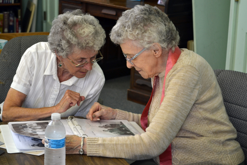 Bridge Academy Class of 1947 graduate Pearl Golden (left) looks through old photographs with sister Doris Trussell Swasey during Golden's 70th class reunion at Bridge Academy in Dresden on Saturday, June 17. (Abigail Adams photo)