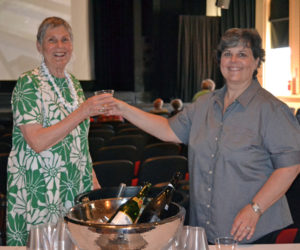 Lincoln Theater member Janet Elwin (left) accepts a glass of prosecco from Sarah Maurer, who poured drinks for attendees during the June 20 open house at Lincoln Theater in Damariscotta celebrating the theater's newly restored vintage windows. (Christine LaPado-Breglia photo)