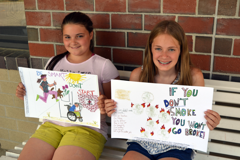 "Emory Shadis (left) and Annie Peaslee, both 11-year-old fifth-graders at Great Salt Bay Community School in Damariscotta, hold up the posters that netted them first and second place, respectively, in the Maine Academy of Family Physicians' staewide ""Tar Wars"" poster contest. (Christine LaPado-Breglia photo)"