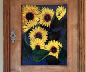 """This painting of sunflowers on a salvaged cupboard door by Florida artist Diane Tonelli is one of many paintings to be on display at the upcoming """"Art in Bloom"""" show at the St. Andrew's Episcopal Church Parish House in Newcastle. (Photo courtesy Ruth Piper)"""