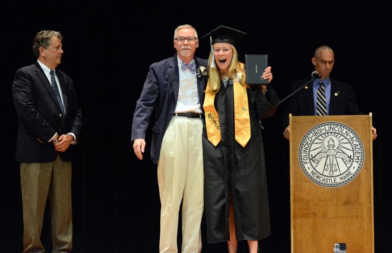 Lincoln Academy senior Esther Martin receives her diploma in a black graduation gown from adviser Robert Breckenridge on June 1, as Head of School David Sturdevant (left) and Associate Head of School Andy Mullin look on. (Photo courtesy Lincoln Academy)