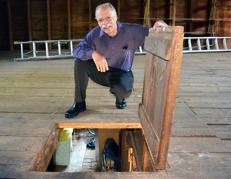 The Rev. Stan LeQuire holds a trap door open in the hay loft of The First Baptist Church of Nobleboro's barn Wednesday, June 7. (J.W. Oliver photo)