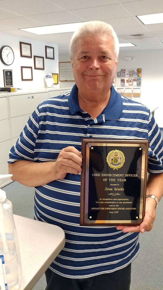 Stan Waltz holds his Code Enforcement Officer of the Year plaque from the Midcoast Code Enforcement Officers Association. (Photo courtesy Julie Keizer)