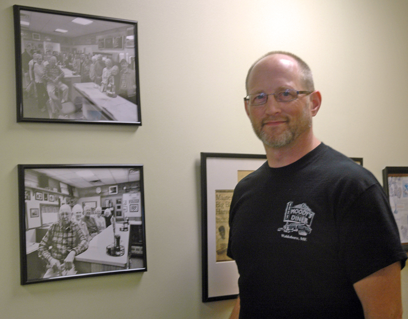 Moody's Diner co-owner Dan Beck, a grandson of founders Percy and Bertha Moody, stands next to photographs of the family. (Alexander Violo photo)