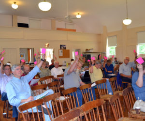 Westport Island voters raise their cards to support an article during annual town meeting at the historic town hall Saturday, June 24. (Charlotte Boynton photo)