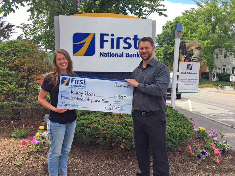 First National Bank Branch Manager Tim Keene presents a check to Hearty Roots Executive Director Haley Bezon.