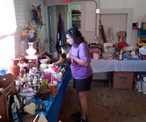 Jeanne Shaw, a volunteer with the Kings Mills Union Hall Association, arranges flower vases and art supplies for the organization's white elephant sale on July 4. (Photo courtesy Lucy Martin)