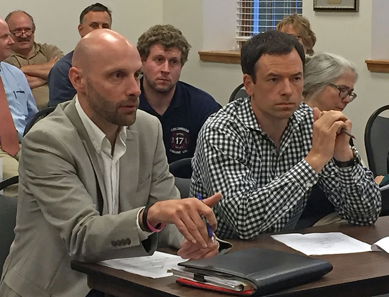 Austin Turner (left) and John Scribner, representatives of the Dollar General and Sherwin-Williams development, discuss the construction timeline during a Damariscotta Planning Board meeting at the town office Monday, July 10. (Maia Zewert photo)