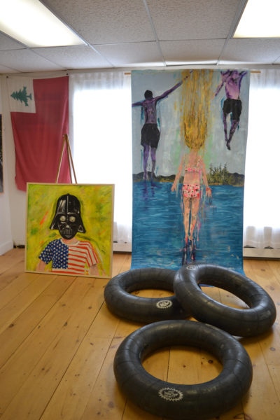 "A huge painting of kids jumping into water, complemented by a trio of inner tubes, stands to the right of ""The Farce is with You,"" at Michael Blaze Petan's current show in the West Gallery of River Arts in Damariscotta. (Christine LaPado-Breglia photo)"