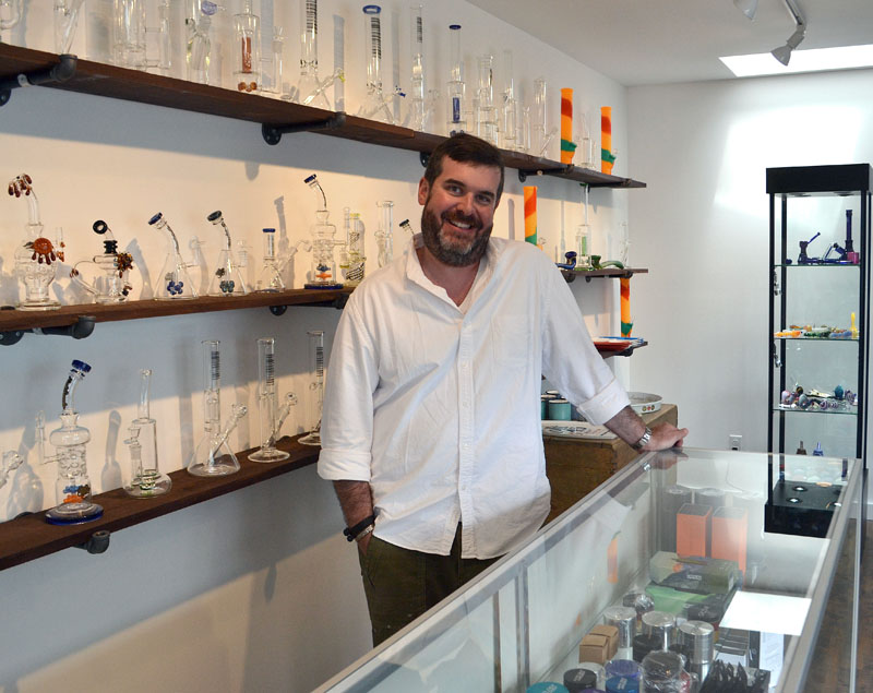 Sea Smoke Shop owner Penn Way stands behind the counter of his new glass pipe store in downtown Damariscotta. (Maia Zewert photo)