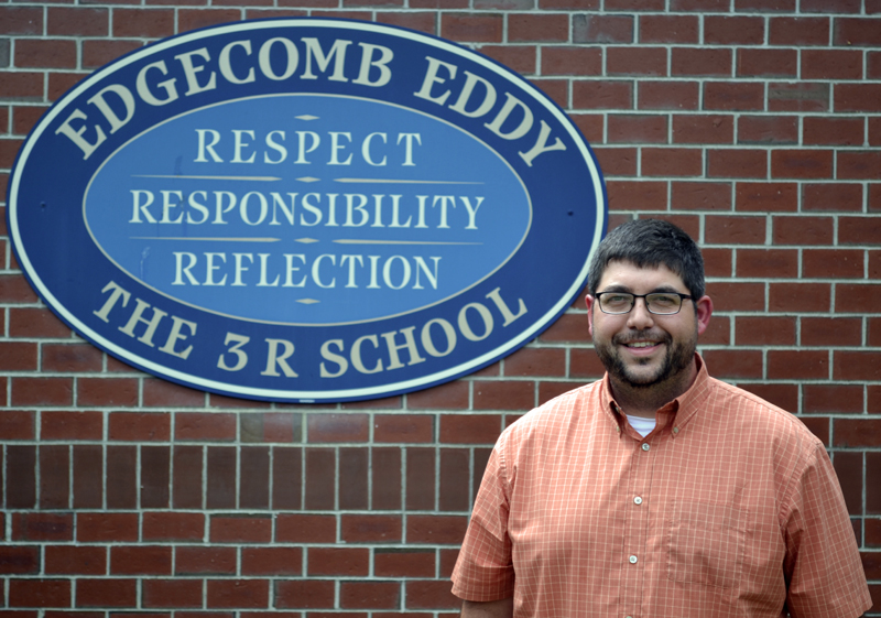 Edgecomb Eddy School Principal Ira Michaud stands in front of the school's sign on Tuesday, July 18, his second day on the job. (Abigail Adams photo)