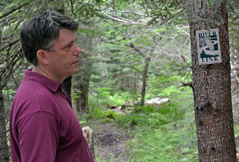 Damariscotta River Association Executive Director Steve Hufnagel looks at the marker for the River-Link Trail on the Barrows Louderback Preserve in Edgecomb on Monday, July 10. (Abigail Adams photo)