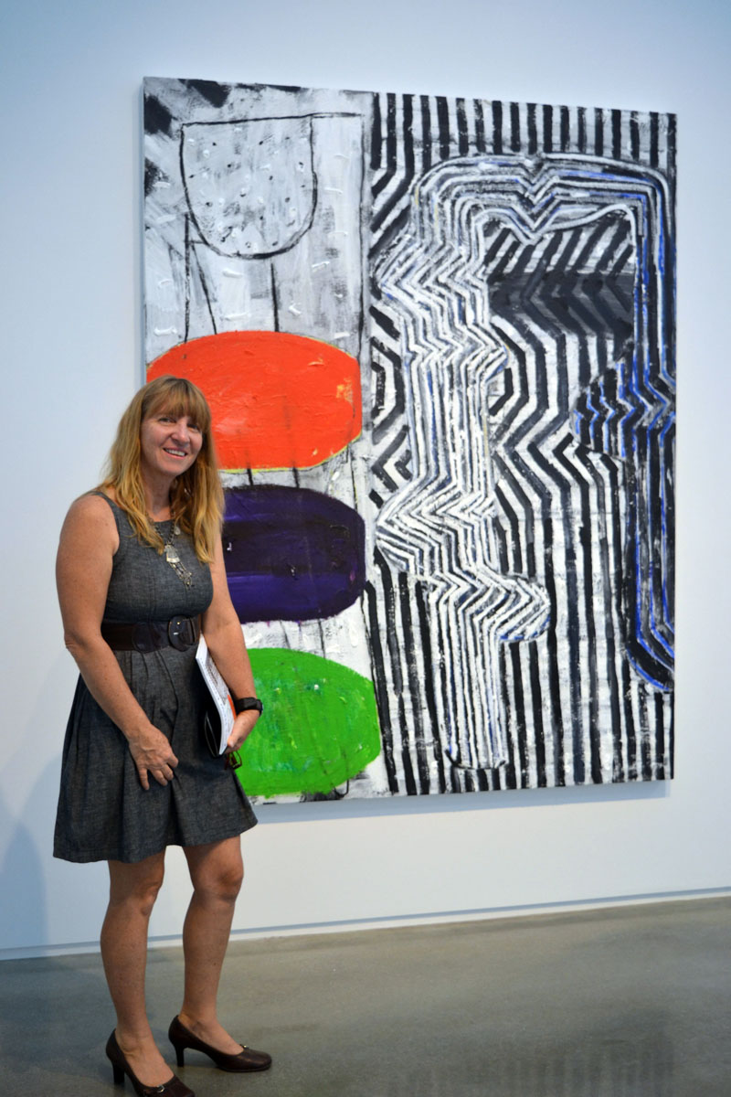 "Jackie Guillerm, wife of Waldoboro artist Philippe Guillerm, stands before ""Move,"" a painting by Seal Point painter John Walker, at the July 20 launch party for Art New England Magazine's July/August issue at the Center for Maine Contemporary Art in Rockland. (Christine LaPado-Breglia photo)"