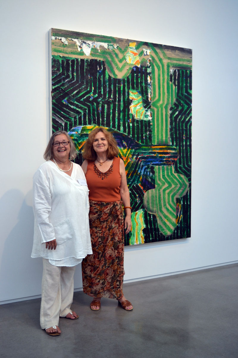 "From left: Yvette Torres, of Yvette Torres Fine Art in Rockland, and Jefferson resident Kay Liss enjoy the festivities at the July 20 launch party for Art New England Magazine's July/August issue. Behind them hangs Seal Point artist John Walker's oil painting titled ""Wait."" (Christine LaPado-Breglia photo)"