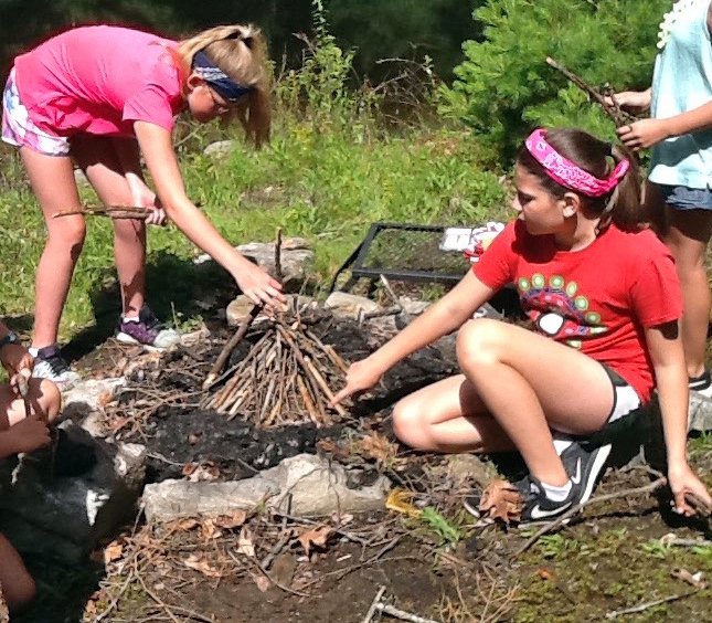 Dez Orne (left) and Kate Murphy learn to build a fire during a Hearty Roots session at the Deck House School in Edgecomb in June. (Photo courtesy Hearty Roots)