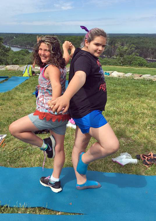 Angie Patriotti (left) and Keanna Pitcher form a yoga pose through teamwork during a Hearty Roots session in Edgecomb. (Photo courtesy Hearty Roots)