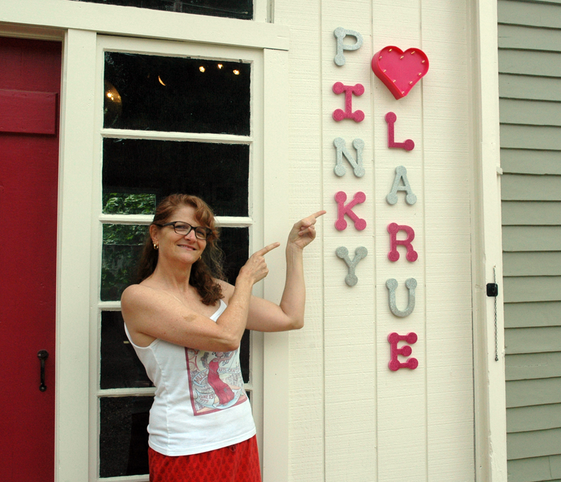 Natalie Masse points to a sign for her vintage store, Pinky Larue. The business will open Saturday, July 8. (Alexander Violo photo)