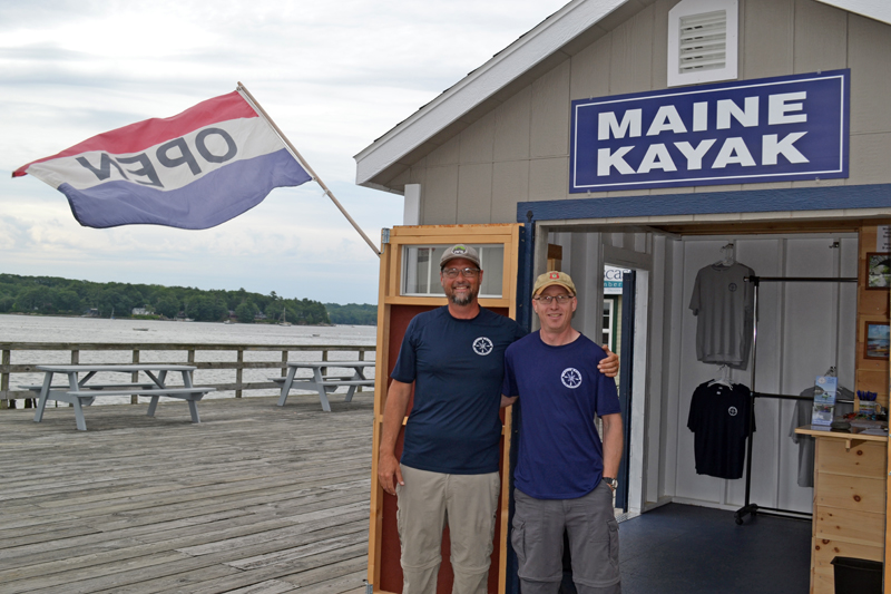 Maine Kayak owner Alvah Maloney and employee Hauns Bassett stand in front of the rental office on the Creamery Pier in Wiscasset on Friday, July 7. (Abigail Adams photo)
