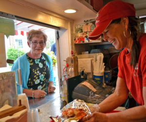 Red's Eats co-owner Debbie Gagnon serves one of the roadside stand's famous lobster rolls to a customer from Bethel on Tuesday, July 25. (Charlotte Boynton photo)