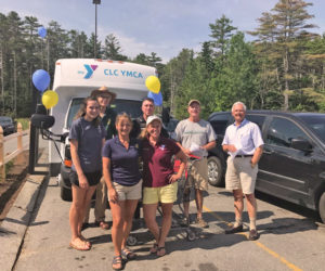 Volunteers help fill the YMCA bus on July 22 at Hannaford Supermarket in Damariscotta to stock the shelves of the Rotary Summer Food for Kids shed.