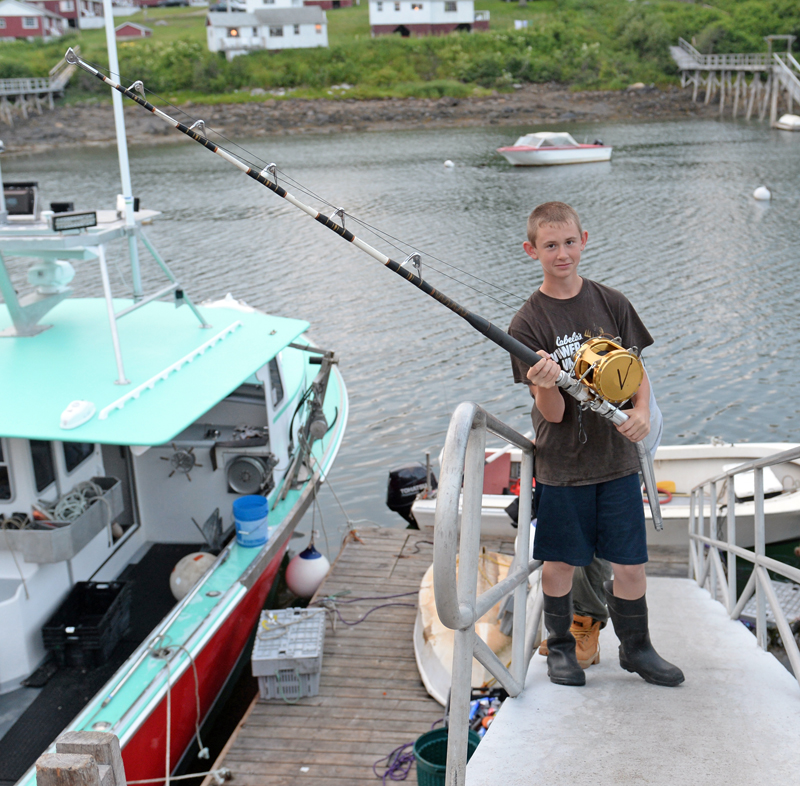 Myles Wotton, 12, with his father's 25-year-old rod and reel, which he used to catch a 450-pound tuna Monday after a five-hour battle. (Paula Roberts photo)