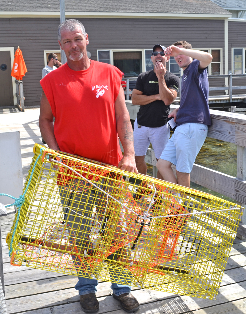 Brent Fogg, one of the organizers of the 31st annual Merritt Brackett Lobster Boat Races, brings a lobster trap to a lottery winner. (Abigail Adams photo)