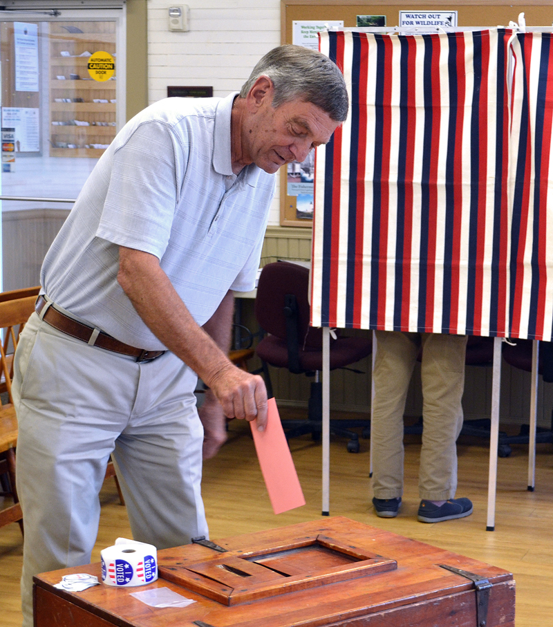 Bristol resident Jim Albright casts his vote during a special town meeting Tuesday, Aug. 22. (Maia Zewert photo)
