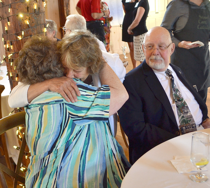 LincolnHealth Director of Volunteers Connie Bright (center) embraces Roberta Watson as Herbert Watson looks on. LincolnHealth will name its new health center for the Watsons, longtime volunteers with the organization. (Maia Zewert photo)