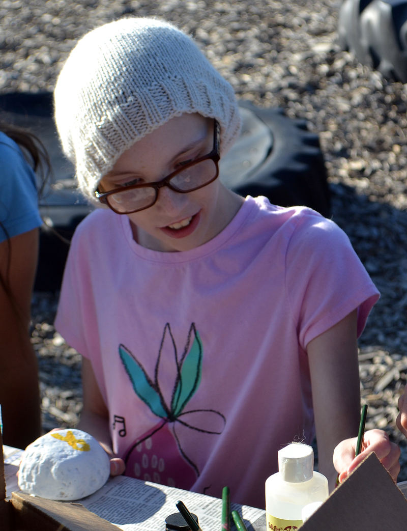 Alice Skiff, of Newcastle, paints a rock with a gold ribbon, the symbol for childhood cancer awareness, at the Great Salt Bay Community School playground Monday, Aug. 28. (Maia Zewert photo)